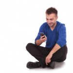 young man sitting and texting on his smartphone